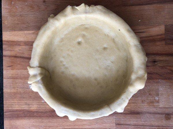 Foncez un moule à pie de 18 cm de diamètre (à défaut utilisez un moule à manqué) avec cette pâte en laissant les bords déborder du moule. Replacez au réfrigérateur.
