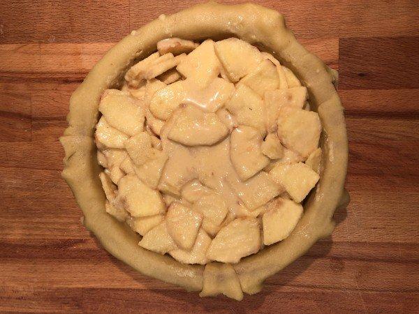Remplissez le fond de tarte avec les pommes enrobées. Arrangez vous pour organiser (un peu) les lamelles de pommes et éviter les trous.