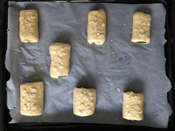 Badigeonnez la surface des pains d'oeuf battu à l'aide d'un pinceau et parsemez d'amandes effilées.