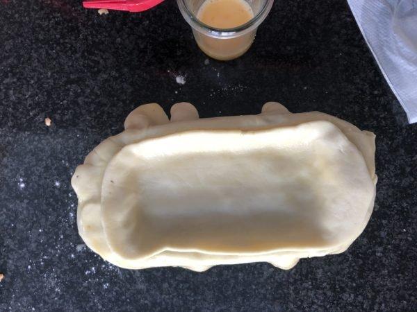 Recouvrez la farce avec le rectangle de pâte, il doit déborder d'environ 1 cm sur la surface de la farce. Badigeonnez au jaune d'œuf la pâte qui dépasse du moule.