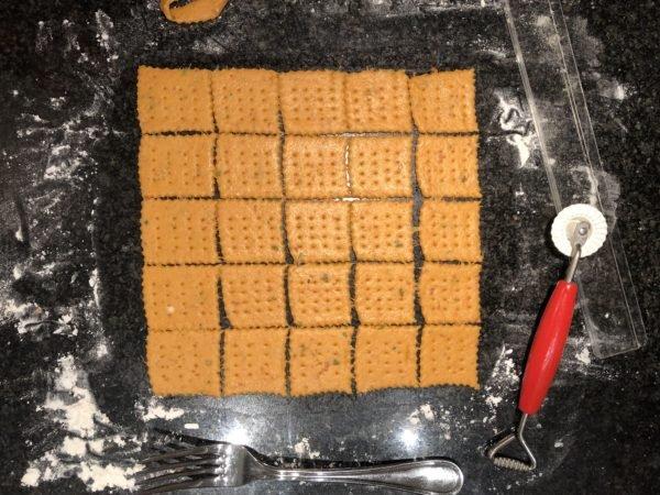 A l'aide d'une roulette dentelée, découpez des carrés de taille similaire. Puis avec un fourchette, piquez la pâte à intervalles réguliers pour décorer les crackers.