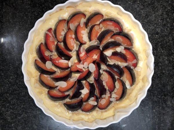 Disposez les quartiers de prunes en rosace sur la crème d'amande. Parsemez d'amandes effilées.
