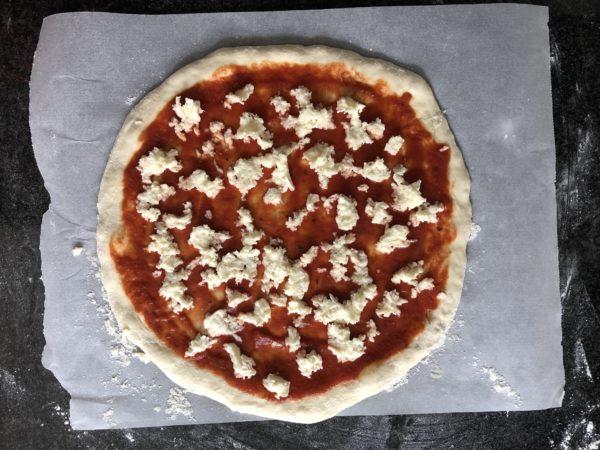 Tartinez la pizza avec la sauce tomate. Recouvrez de mozzarella râpée.