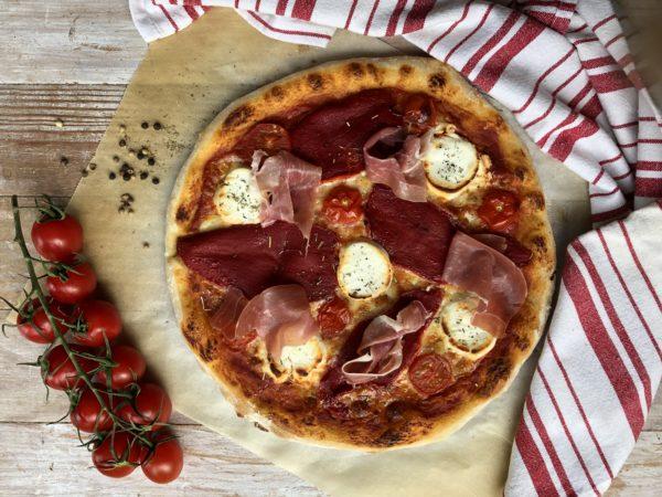 Sortez la plaque bouillante du four. Faites glisser la pizza dessus et enfournez immédiatement pour 10-15 min selon la coloration qui vous fait envie.