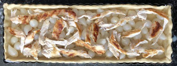 Répartissez les lamelles d'oignon et le poulet rôti sur le fond de tarte.