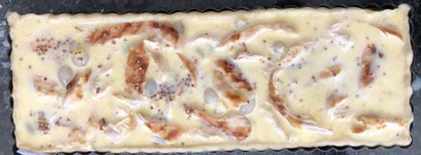 Fouettez les oeufs avec le lait et la moutarde à l'ancienne. Versez cette préparation sur le fond de tarte.