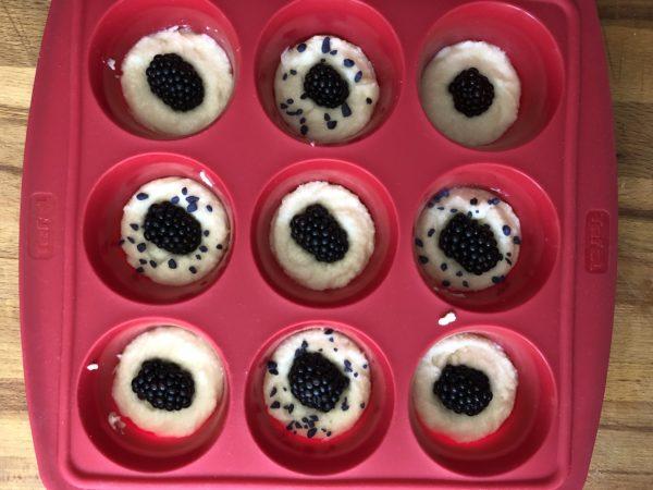 Versez dans des empreintes à muffins. Enfoncez une grosse mûre au centre de chaque financier.