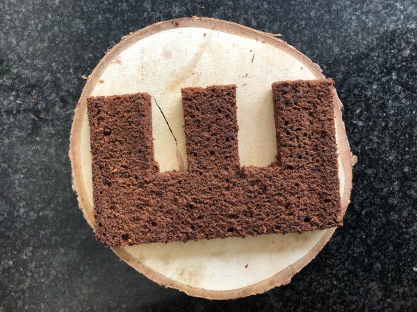 Coupez le gâteau en deux dans l'épaisseur. Coupez proprement les bords et taillez le gâteau en forme de E.