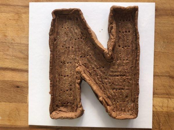 Etalez la pâte entre deux feuilles de papier sulfurisé, détaillez le N à l'aide de la forme du kit. Avec les chutes de pâte, découpez des bords que vous soudez au N. Renforcez le contour à l'aide de papier aluminium plié. Cela évitera qu'ils s'affaissent à la cuisson . Piquez le fond de pâte avec une fourchette. Réservez au frais 30 minutes (cela évitera à la pâte de se rétracter à la cuisson).