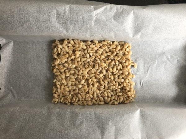 Découpez deux grands rectangles de papier sulfurisé. Au milieu, répartissez l'orge cuit, puis les tagliatelles de courgettes par dessus.
