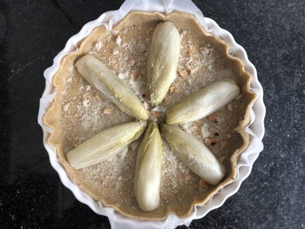 Coupez les endives en deux dans la longueur et répartissez les sur le fond de pâte.