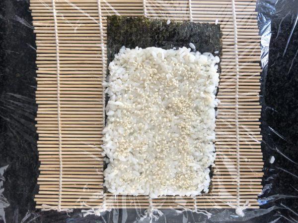 Déposez la feuille d'algue sur la natte, recouvrez la de riz et saupoudrez de sésame.