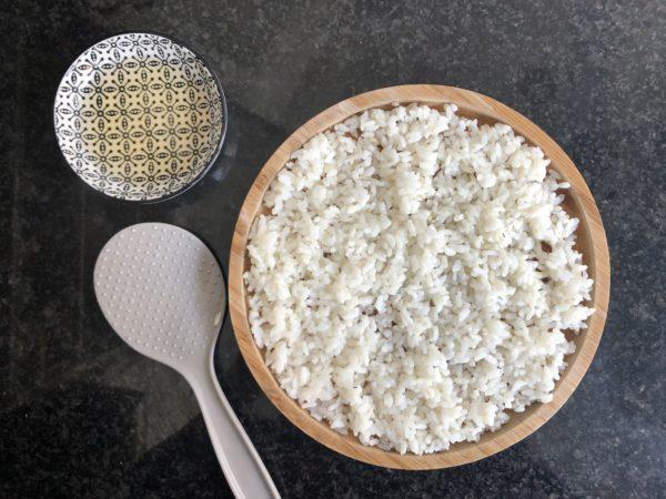 Répartissez le riz cuit à plat dans un grand tupperware. Puis arrosez ensuite avec la sauce et mélangez délicatement.
