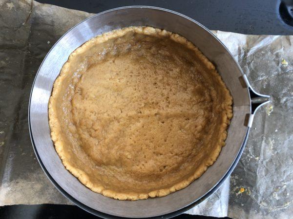 Garnissez un moule à charnière de 16 cm de diamètre chemisé en papier sulfurisé avec cette pâte en l'écrasant à l'aide de vos doigts. Faites un bord de 4 cm de haut.