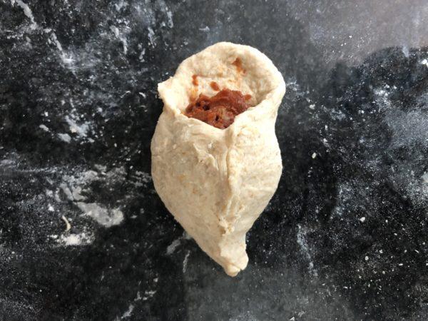 Déposez une boule de farce au centre (la cuillère à glace est parfaite pour bien portionner) et repliez la pâte par dessus.