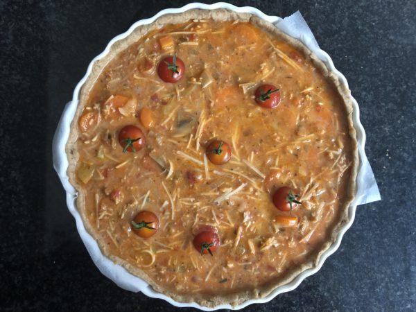 Versez la garniture sur le fond de pâte. Enfoncez les tomates cerises à intervalles réguliers dans la garniture.