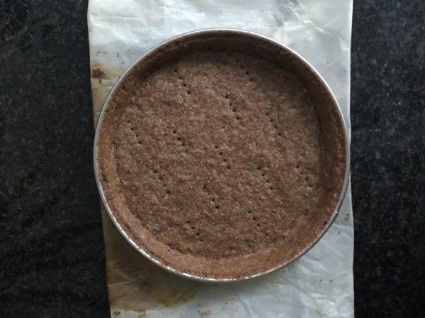 Foncez un moule à tarte de 18 cm de diamètre et faites cuire 25 min avec un poids par dessus.  Laissez refroidir totalement.  En même temps, faites cuire les chutes de pâte sur du papier sulfurisé.