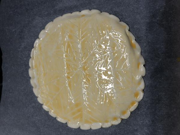 Retournez la galette sur une plaque de cuisson garnie de papier sulfurisée. Badigeonnez le dessus d'oeuf battu. A l'aide d'un couteau pointu et bien aiguisé, incisez le motif de votre choix sur la galette (ici une sorte de flocon/chevron).