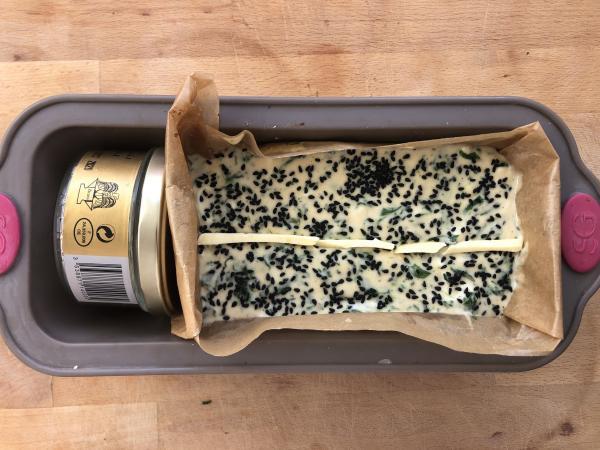 Versez la pâte dans un moule à cake de 26 cm de long et parsemez de quelques graines de nigelles.