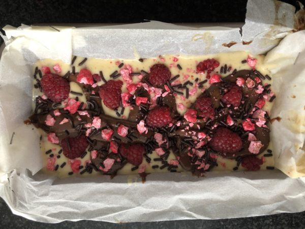 Pochez les deux pâtes alternativement dans le moule à cake. Dès que vous versez de la pâte claire, parsemez avec des framboises fraiches. Alternez les couches en les superposant de manière aléatoire pour réaliser l'effet marbré.