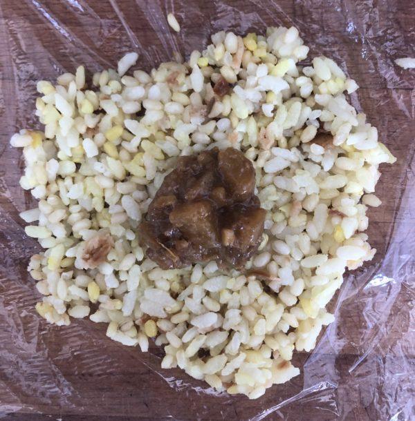 Divisez le riz en 4 parts. Déposez une part sur une feuille de film étirable. Creusez un puits au centre et déposez une grosse noix de chutney.
